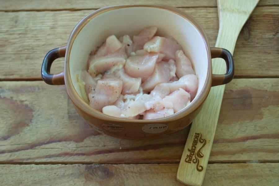 Обжаренный лук выкладываем в смазанный маслом горшочек или такую кастрюльку как моя. Поверх лука выкладываем нарезанное мясо птицы. В качестве мяса можно использовать не только филе, но и мясо с ноги. Главное без костей. Мясо нужно посолить и поперчить.