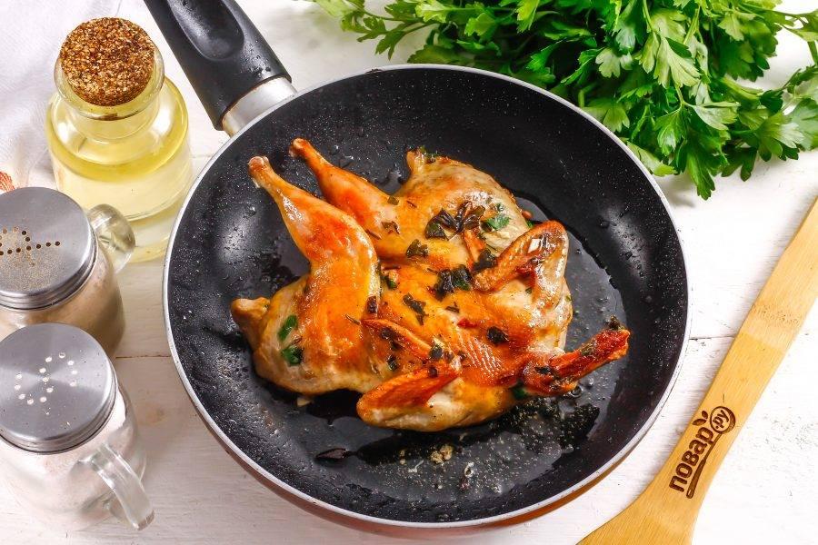 Спустя указанное время прогрейте растительное масло в сковороде и выложите тушку перепела кожей вниз. Обжарьте на среднем нагреве примерно 5-7 минут до румяности. Затем тушку переверните, убавьте нагрев до минимума, накройте сковороду крышкой и обжарьте тушку еще 10-12 минут до румяности с другой стороны. За это время перепел пропарится и поджарится.
