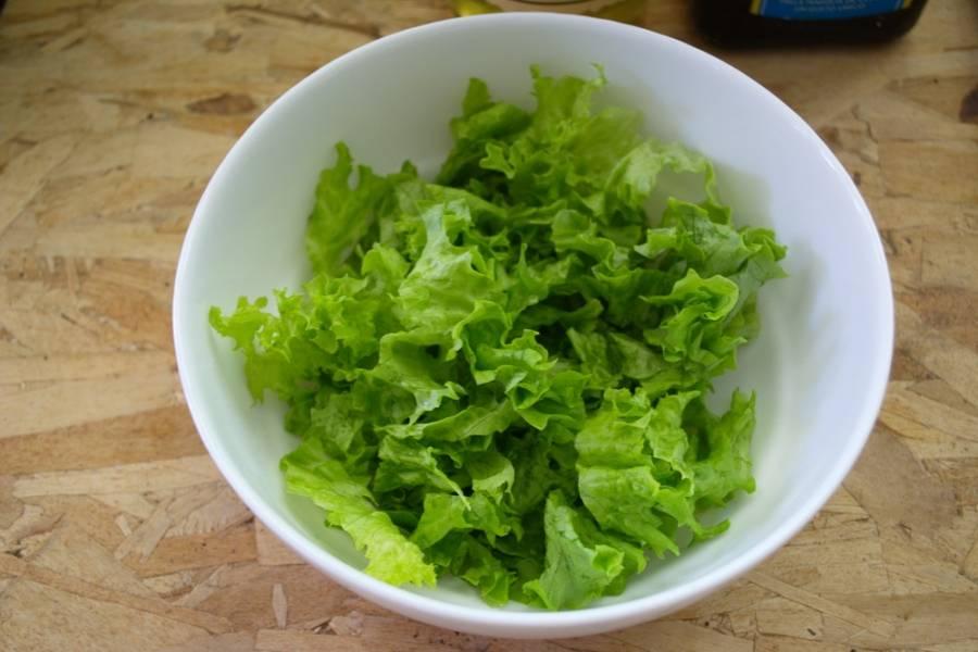 Салатные листья промыть, промокнуть от влаги и, порвав руками на кусочки, выложить в миску.