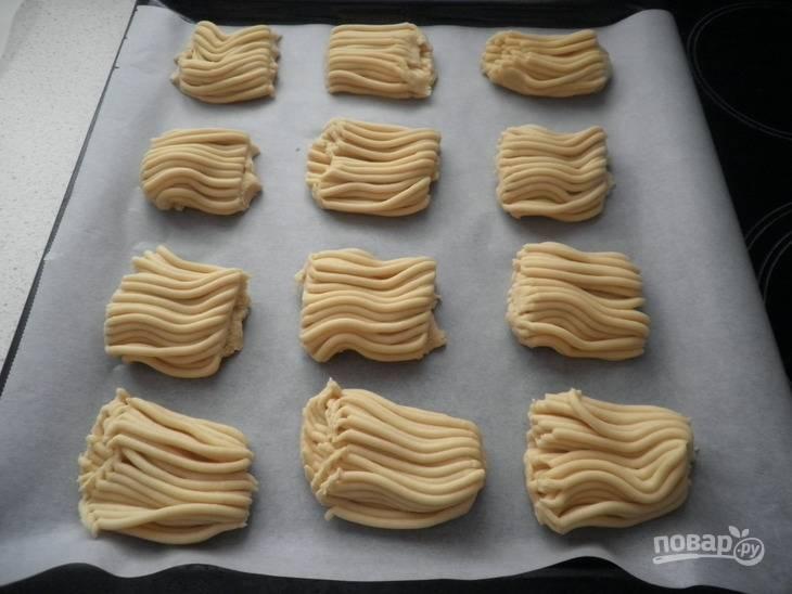 6.Получившиеся «кудри» из теста обрезайте по желаемому размеру (около 8-10 см). Уложите печенье на противень с пергаментом.
