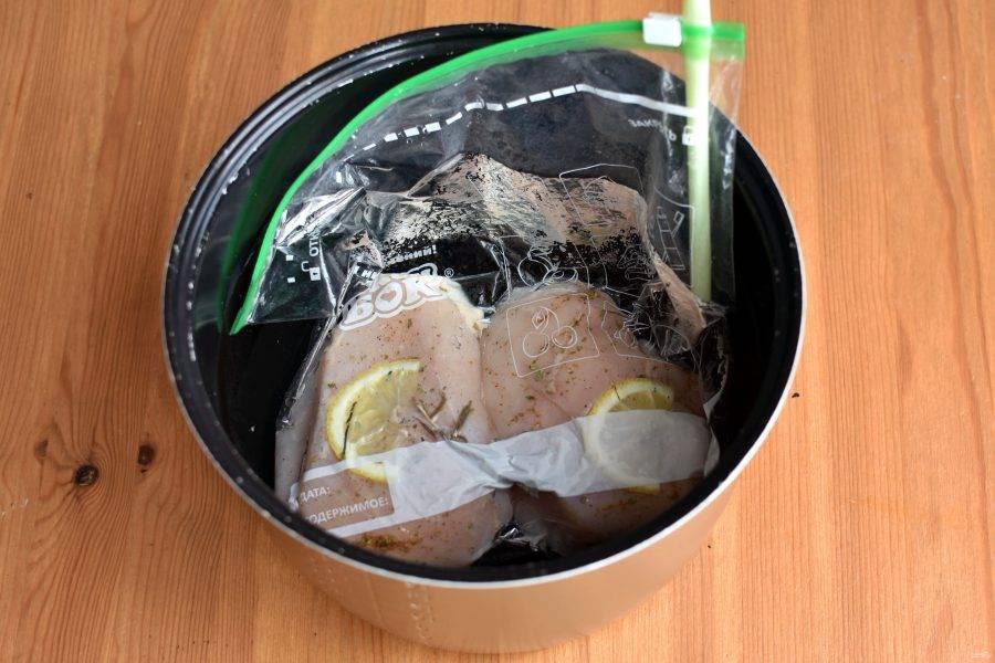 Возьмите пакет с зип-застежкой и уложите в него оба филе. Добавьте веточку розмарина. Налейте холодной воды в подходящую емкость и опустите пакет так, чтобы филе было ниже уровня воды. Вода вытеснит воздух из пакета. Вставьте трубочку для коктейля в уголок пакета и закройте застежку до трубочки. Руками обожмите остаток воздуха и быстро выдерните трубочку, застегнув замок до конца.