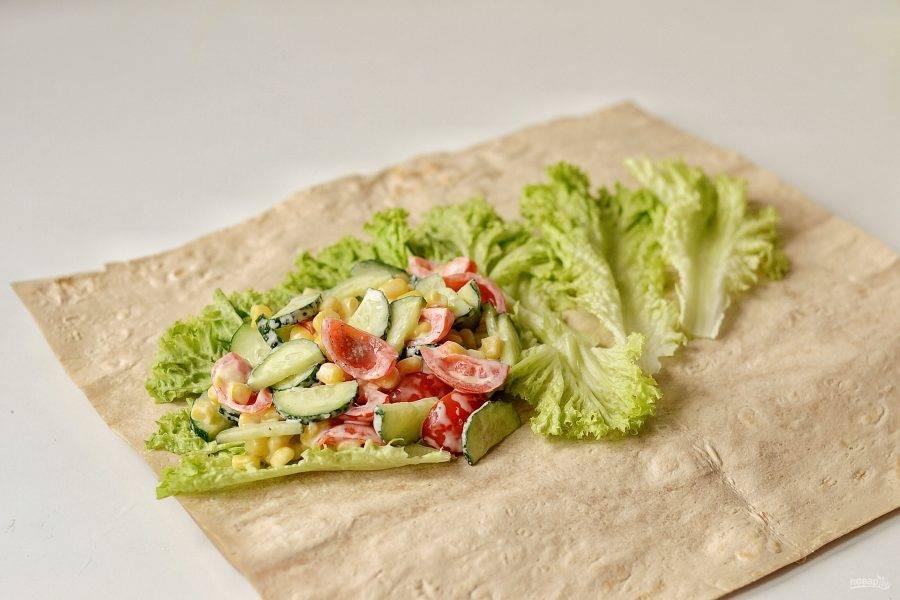 Выложите на лаваш листья салата, сверху овощную начинку. Скрутите лаваш в ролл.