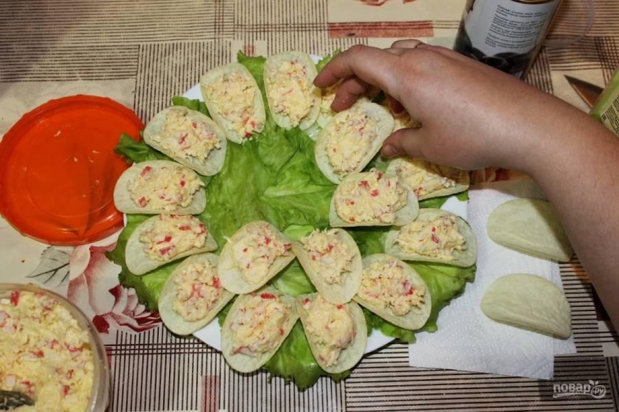 Выкладываем на тарелку листья салата. Сверху кладем чипсы, накладываем на них начинку.