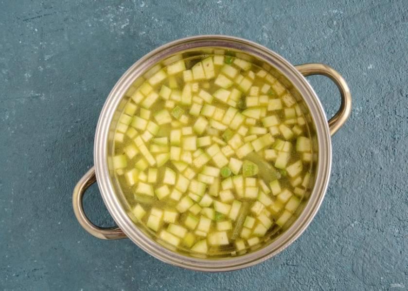 Жарьте ещё пару минут, затем залейте бульоном и готовьте суп 10 минут. Посолите по вкусу.