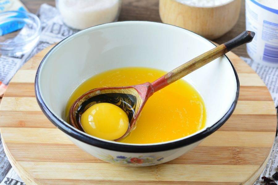 Растопите сливочное масло и остудите его. Затем вбейте куриное яйцо.
