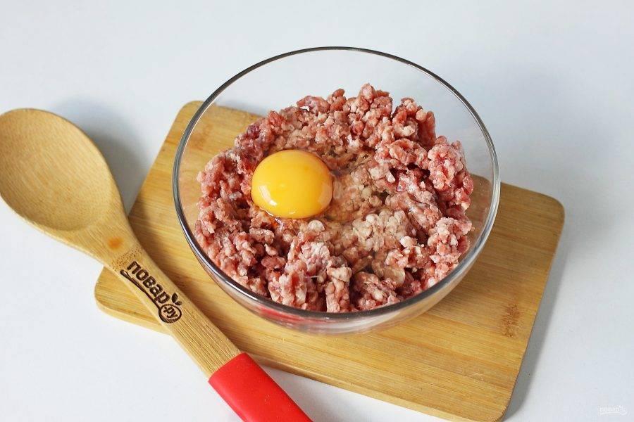 Переложите фарш в глубокую миску. Добавьте яйцо.