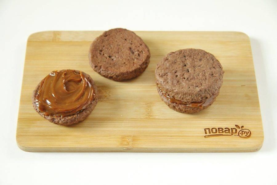 Промажьте печенье вареной сгущенкой и накройте вторым печеньем.
