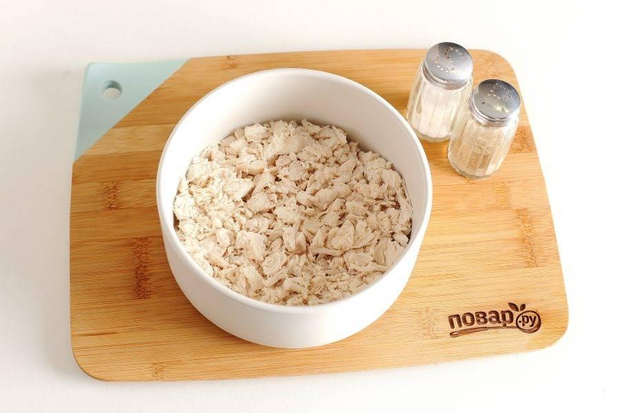 Салат можно выложить в глубокий салат или сформировать при помощи кулинарного кольца. Первым слоем положите куриное филе. Смажьте курицу майонезом, посолите и поперчите по вкусу.