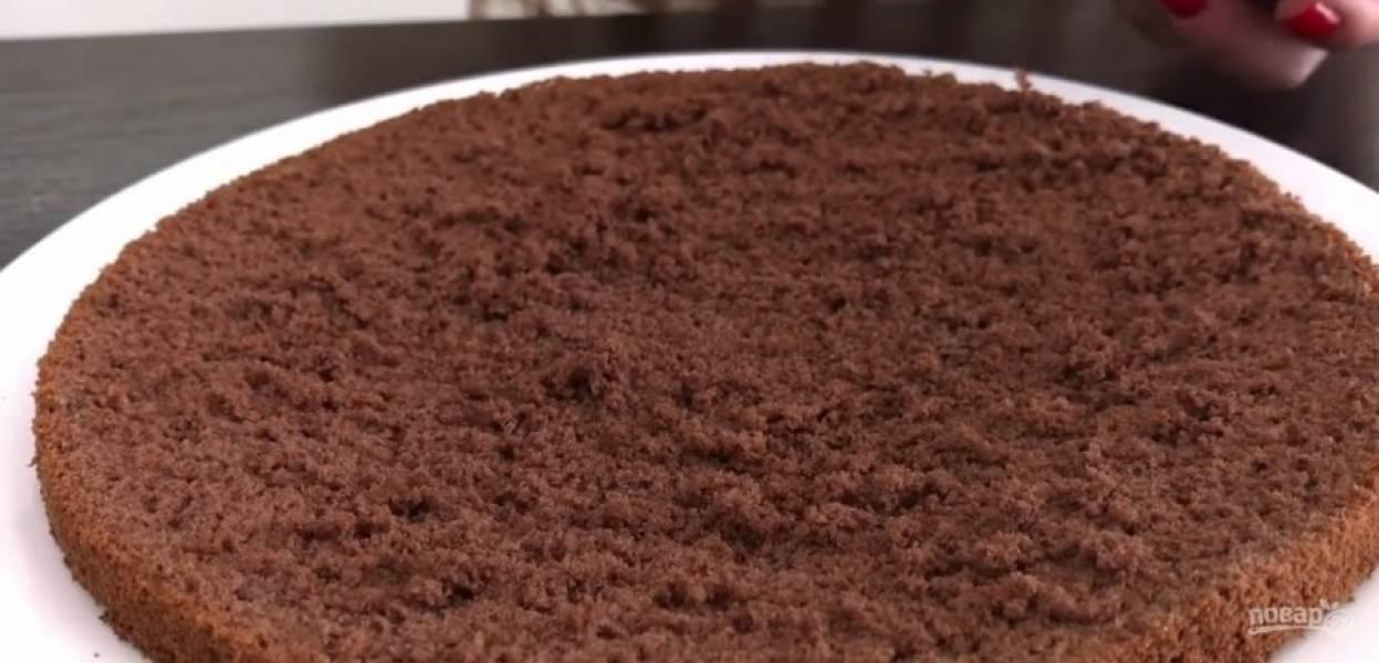4. Смешайте масло с вареной сгущенкой и просеянным какао. Снова взбейте. Добавьте подсолнечное масло, не прекращая взбивать. Орехи измельчите блендером до крупной крошки. Разделите корж на три части.