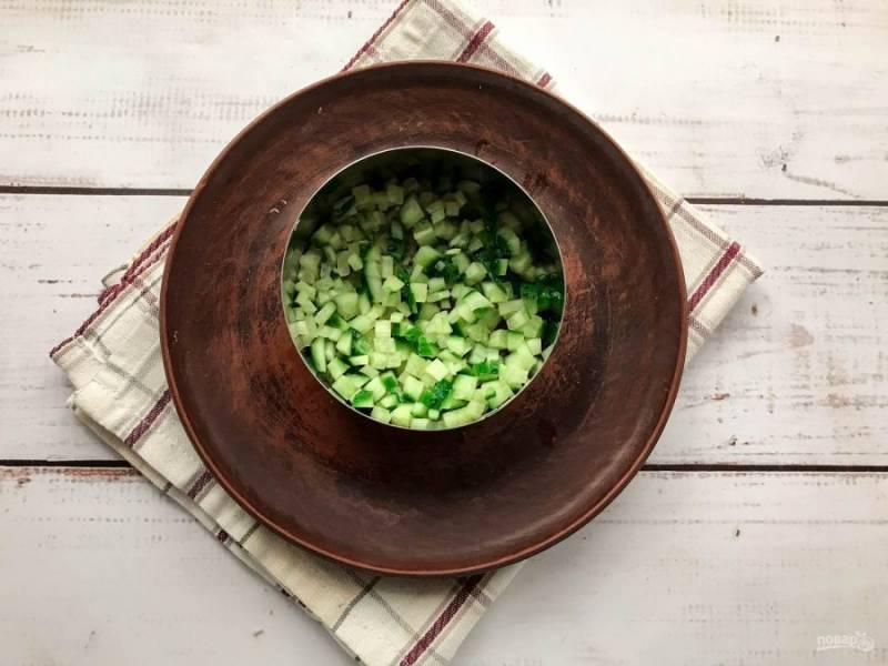 Возьмите сервировочное кольцо и выложите его на тарелку. Огурцы хорошо помойте, обсушите бумажным полотенцем, мелко нарежьте и выложите на дно тарелки. Каждый слой смазывайте небольшим количеством майонеза. Огурцы немного посолите.