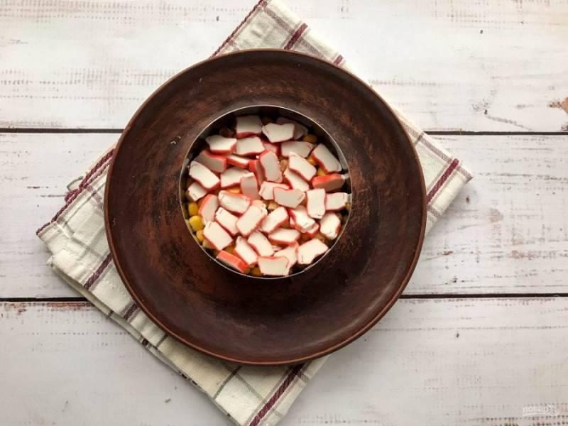 Крабовые палочки нарежьте кружочками и выложите поверх кукурузы.