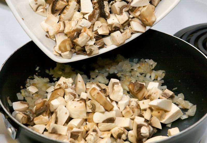 2. Тем временем вымыть и очистить грибы. Нарезать небольшими кусочками и отправить на сковороду к луку.
