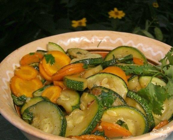 5. Обжаренные цукини соедините с кружочками моркови в сковородке. Добавьте к ним зелень. Положите чеснок. Перемешайте. Салат прогрейте на сковородке пару минут. Посолите по вкусу. Готовый салат подавайте теплым, посыпьте молотым перцем и добавьте сок лимона. Приятного аппетита.