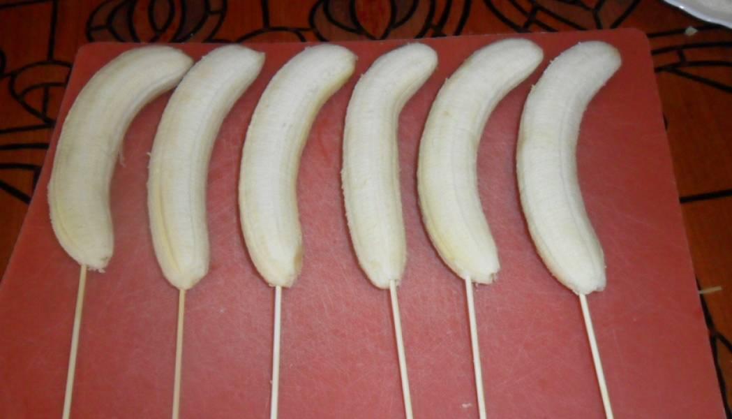 Очищаем бананы от кожуры. Вставляем в бананы деревянные шпажки или палочки. Постарайтесь аккуратно просунуть палочку как можно дальше, чтобы она хорошо зафиксировалась и банан не слетел.