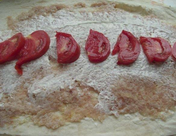 7. Снова немного соуса. Добавить в классический рецепт лаваша с фаршем и сыром также можно овощи, в данном случае - это нарезанные помидоры.