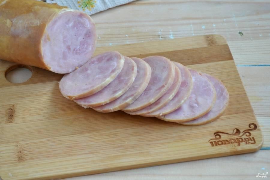 Колбасу (ветчину) порежьте тонкими кружками.