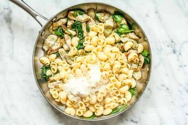 4. Затем выложите к ним макароны. Добавьте сыр и специи по вашему вкусу. Выдавите чеснок, добавьте в самом конце, как и смесь из сухарей и миндаля.