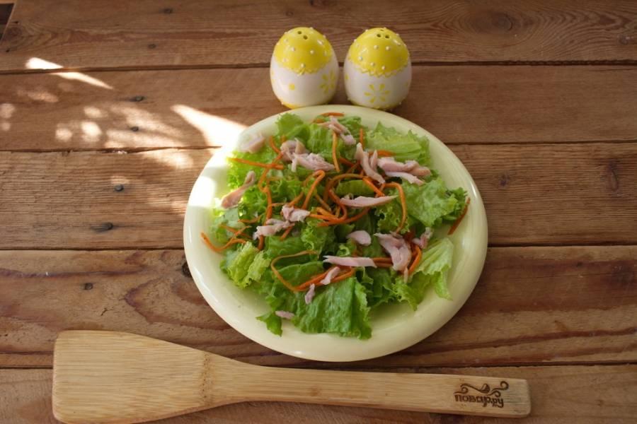 Мясо курицы снять с кости, удалить кожу. Мякоть нарвать руками на тонкие волокна. Разложить на салатных листьях.