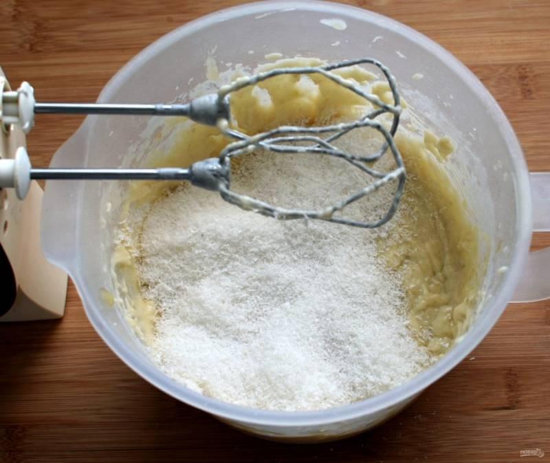 Добавьте просеянную с разрыхлителем муку, соль и ванилин. Вымешивайте тесто на низких оборотах миксера. Всыпьте половину кокосовой стружки и перемешайте.