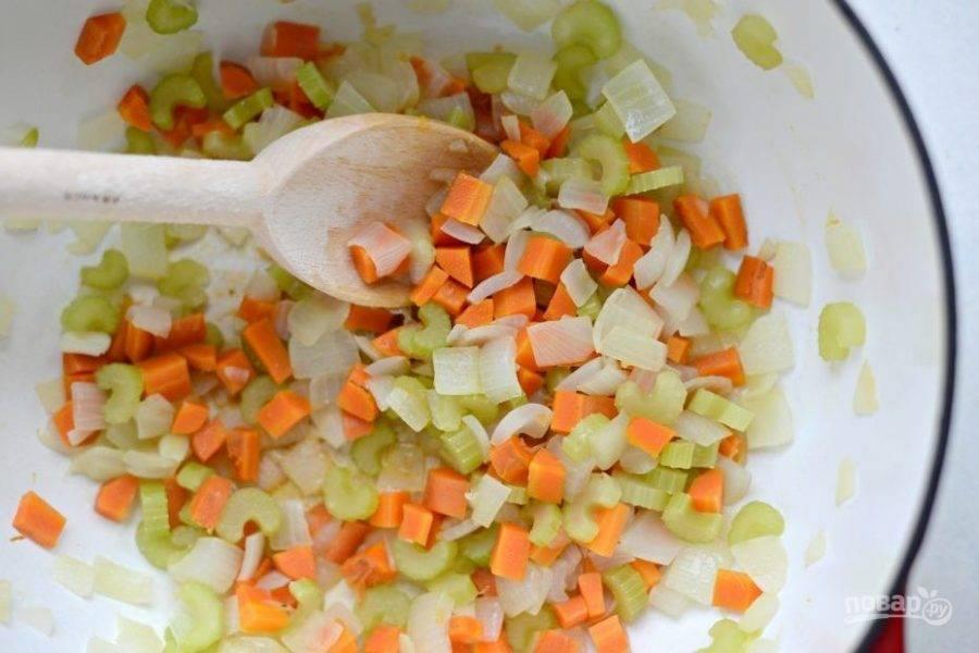 Теперь займитесь супом. Нашинкуйте мелкими кубиками морковь, сельдерей и лук. Потом обжарьте кусочки в разогретом масле в течение 13 минут, помешивая. В конце добавьте измельчённый чеснок.