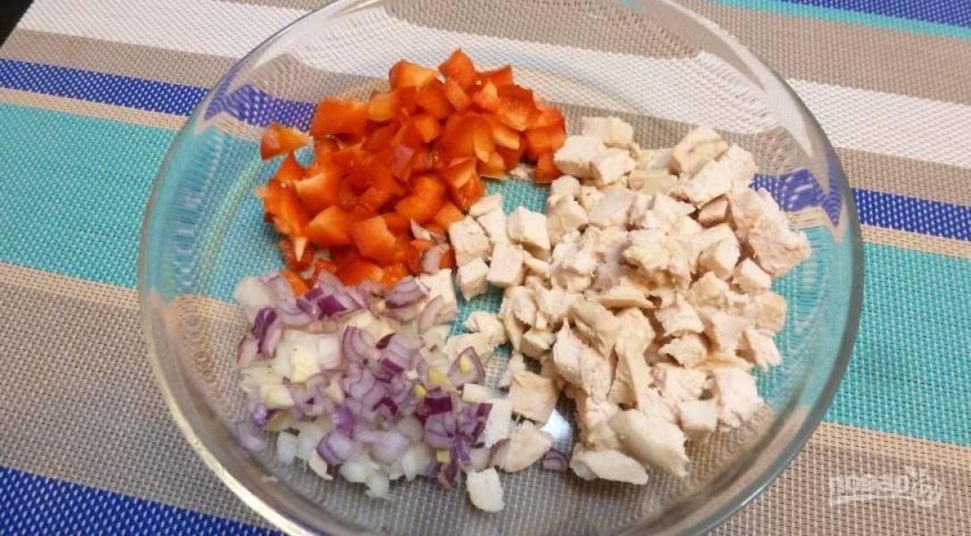 Куриную грудку отварите в подсоленной воде до готовности. Затем нарежьте её кубиками вместе с перцем и луком.