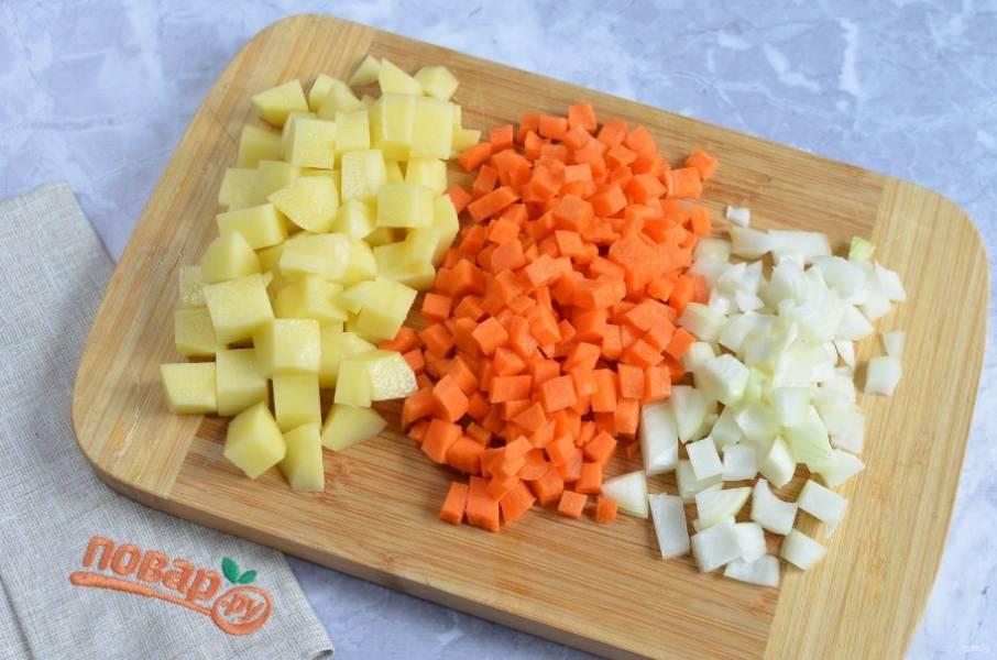2. Подготовьте овощи: очистите лук, морковь и картофель. Порежьте овощи кубиками. Положите в готовый бульон и варите 20 минут.