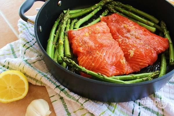 3. На сковороду выложите филе рыбы в центр, а по бокам - спаржу. Вылейте ароматное масло, распределив по рыбе и овощам равномерно. Накройте крышкой и томите минут 10 на среднем огне.