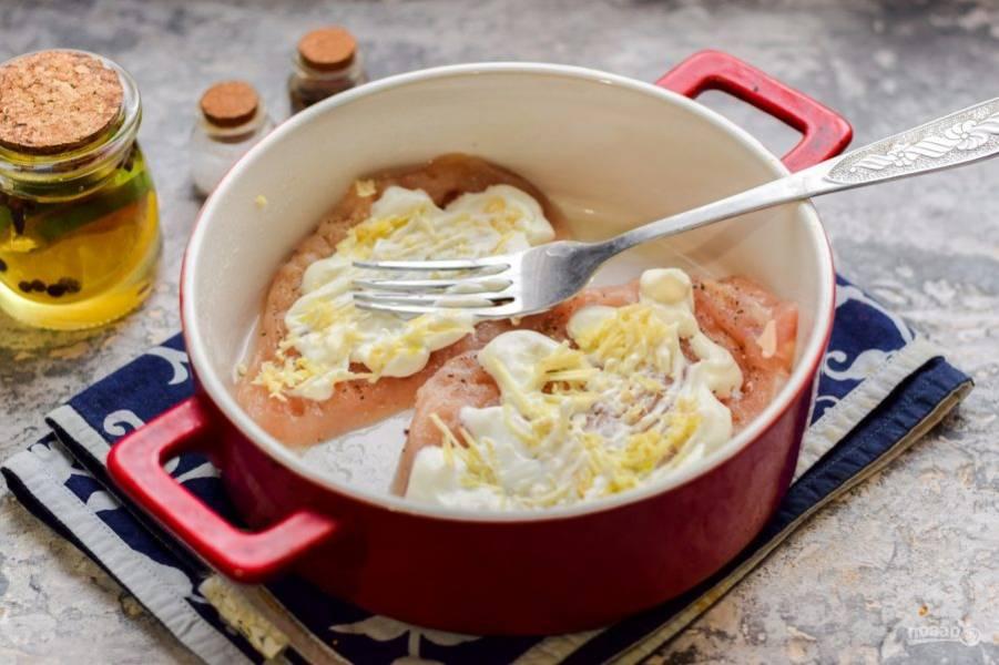 Смажьте курицу йогуртом и измельченным чесноком.