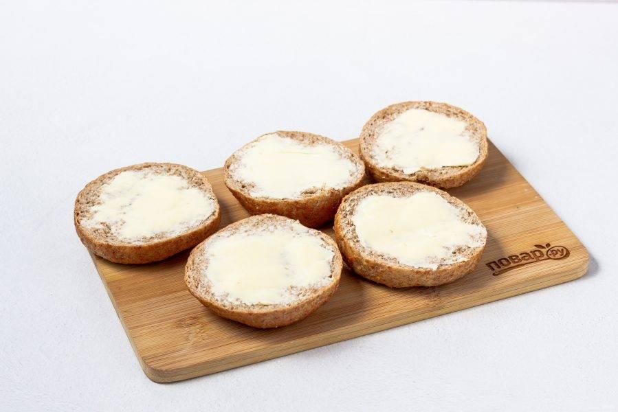 Хлебцы разрежьте вдоль пополам и намажьте сливочным маслом.