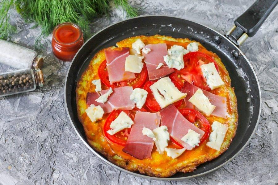 Выложите на кабачковую основу в любом порядке вяленое мясо или колбасные изделия, нарезанный помидор, сыр. Можно использовать любой плавкий сорт сыра, который есть у вас в наличии. Накройте сковороду крышкой и обжаривайте пиццу до румяной корочки снизу и до расплавления сыра.