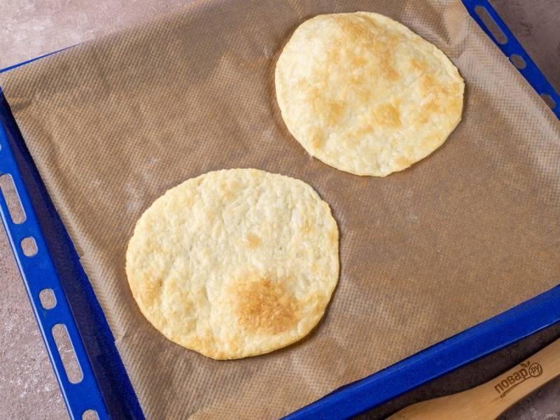 Обрезок теста, который получился при вырезании тарелкой, соедените со следующим оберзком и снова раскатайте, чтобы получить новый корж. Действуйте таким образом, пока тесто не закончится. Готовые коржи (или корж, если большой) кладите на противень с пекарской бумагой. Выпекайте до румяности в разогретой до 200 градусов духовке 7-8 минут.