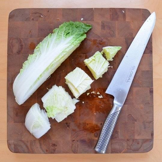 Порежьте предварительно мытую капусту на четвертинки, удалите кочерыжку. Далее четвертинки нарежьте вдоль пополам.