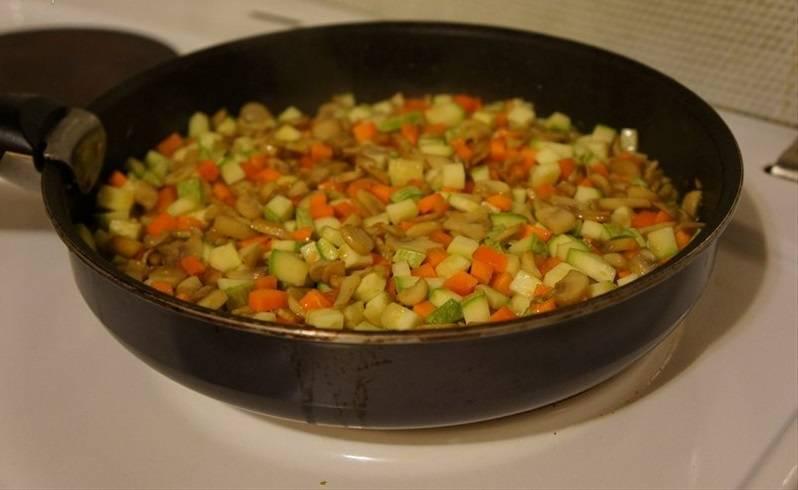 В поджаренные грибы добавьте морковку и кабачки.