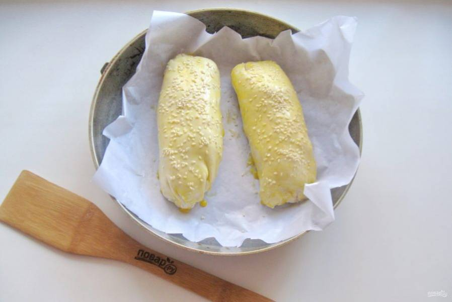 Смажьте пироги желтком и посыпьте кунжутом.