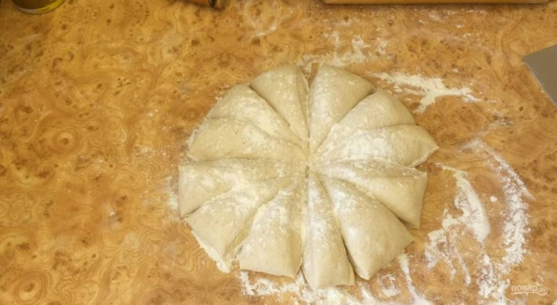 4. Выложите тесто на рабочую поверхность, присыпанную мукой, и округлите. Разделите тесто на две части, одну из них накрыв пленкой. Разделите часть теста на 12 частей и округлите.