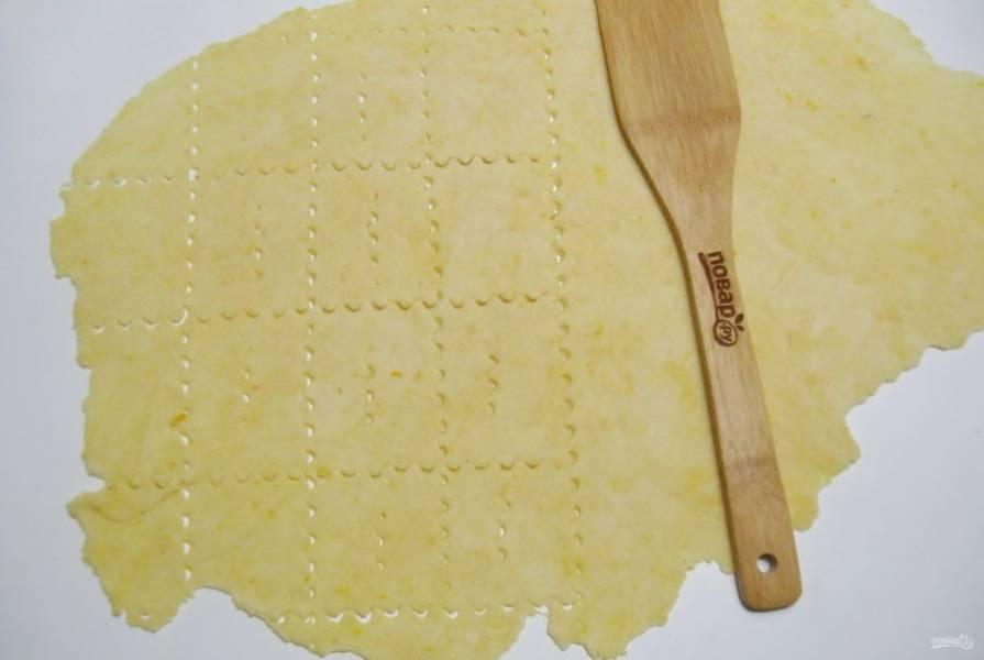 Раскатайте тесто толщиной 2-3 мм на столе, посыпанном мукой. Нарежьте на квадраты или прямоугольники. В центре сделайте разрез.