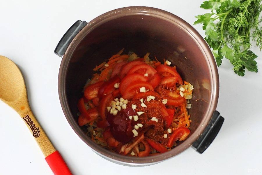 Добавьте перец, нарезанный небольшой соломкой, нарезанный дольками помидор, томатную пасту, измельченный чеснок и специи. Обжарьте все вместе в течение 3-5 минут.