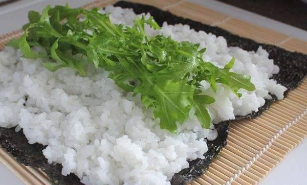 На лист нури выложите рис, на него рукколу.