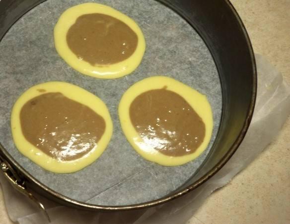 Форму для выпечки застелите бумагой. Немного смажьте её маслом. Теперь нужно правильно распределить тесто. Сделайте 3 лепёшки из светлого теста, а в них влейте немного тёмного.