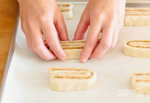 8. Выложите их на противень, застеленный пергаментом, срезом вверх. Отправьте слоечки в разогретую до 200 градусов духовку.