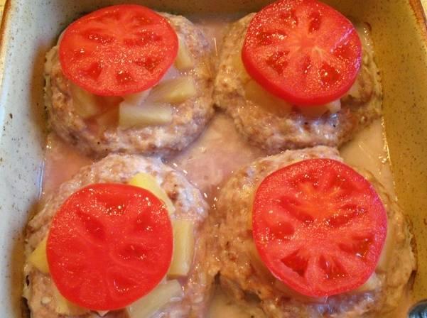 По истечении времени форму из духовки извлекаем и кладем на каждый биточек по кружочку помидора.