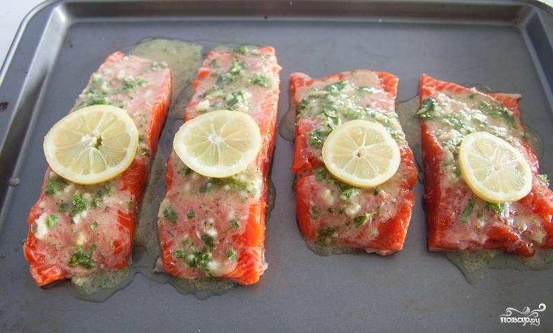 На каждый кусочек рыбы выкладываем ломтик лимона.