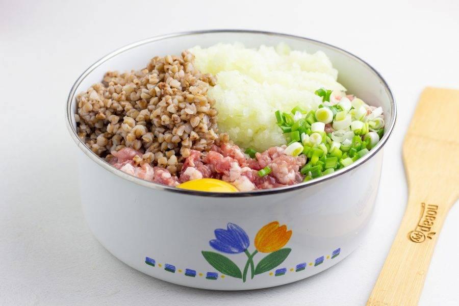 В фарш добавьте репчатый лук, натертый на мелкой терке или пробитый блендером, половину рубленной зелени, сырое яйцо и готовую гречку. Всё тщательно перемешайте, посолите и поперчите по вкусу.