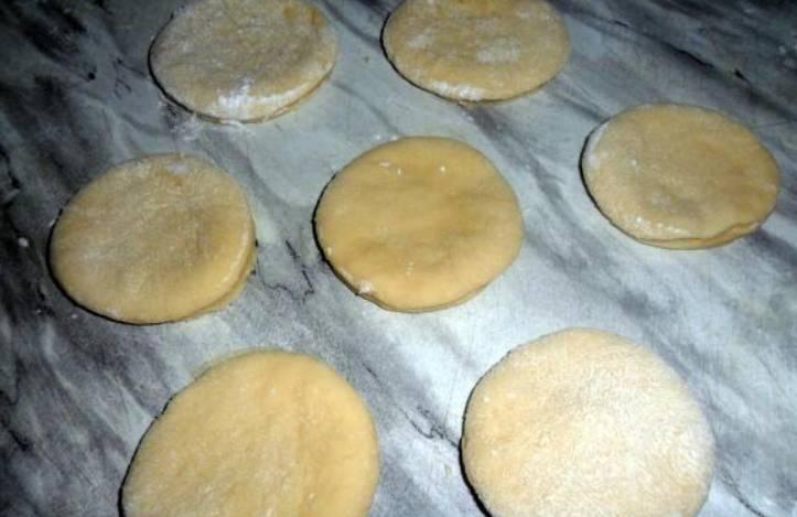 Раскатываем тесто в пласт толщиной 1 см. При помощи стакана вырезаем кружочки.