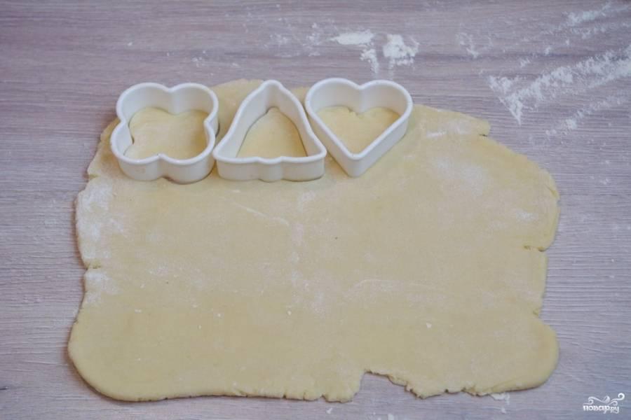 Через полчаса достаньте тесто и разделите его на 3 части. Так удобнее будет с ним работать. Каждую часть раскатайте в пласт по 0,5 см. толщиной. При помощи формочек для печенья вырезаем фигурки.