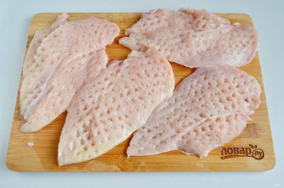 2. Каждое филе разрежьте вдоль на две части. Отбейте хорошо молоточком.
