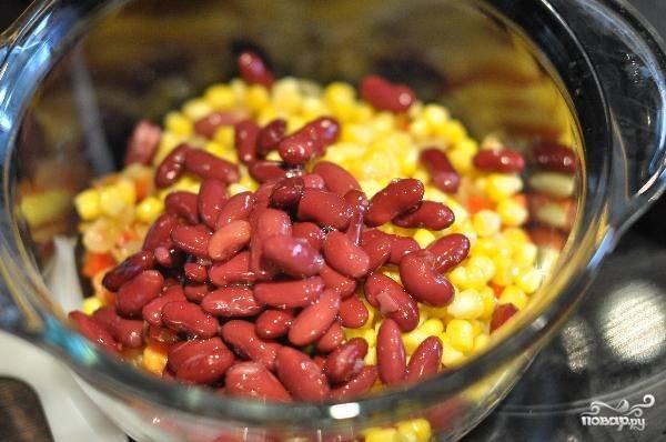 Вскрываем банки с консервированными фасолью и кукурузой. Сливаем с них жидкость, а зерна высыпаем в глубокую миску.