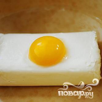 Положить в миску плавленый сыр. Добавить яичный желток.