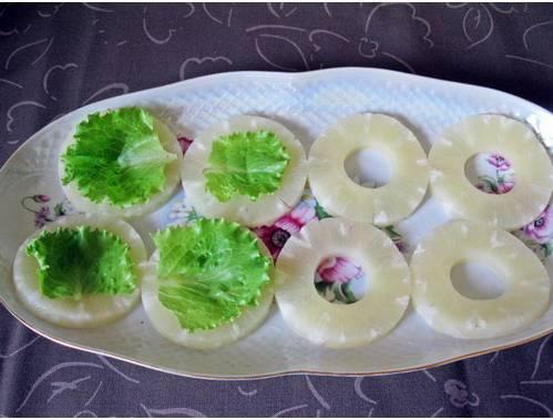 1. Кольца ананасов достаем и банки и обсушим бумажными полотенцами. Поверх ананаса - листья салата. Выкладываем на блюдо. Параллельно отвариваем и остужаем яйца.