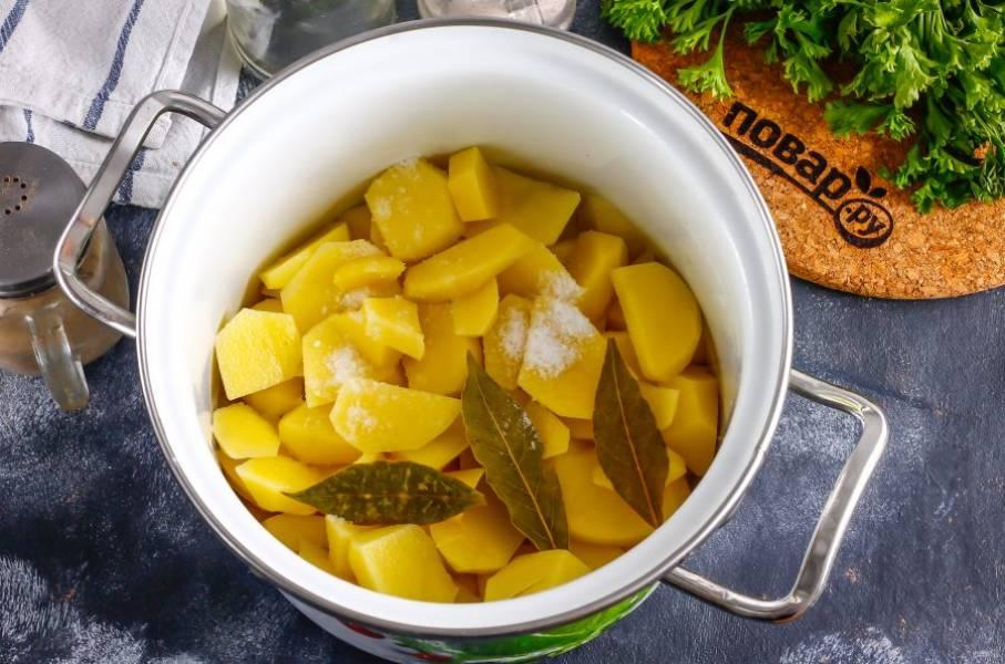 Нарежьте картофель ломтиками в кастрюлю, всыпьте туда же соль и лавровые листья, влейте горячую воду и поместите емкость на плиту.